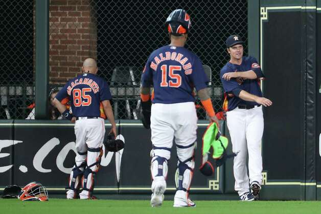 Houston Astros starting pitcher Zack Greinke (21) warms up with catcher Martin Maldonado (15) and catcher Javier Bracamonte (85) walks out to the bullpen before a major league baseball game against the San Diego Padres Sunday, May 30, 2021, at Minute Maid Park in Houston. Photo: Brett Coomer, Staff Photographer / © 2021 Houston Chronicle