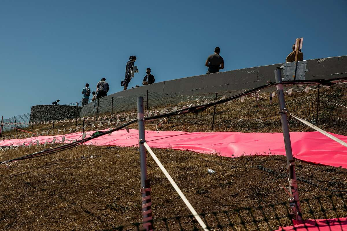 Visitors stand in the viewing area above the Pink Triangle Memorial on the slope of Twin Peaks in San Francisco.