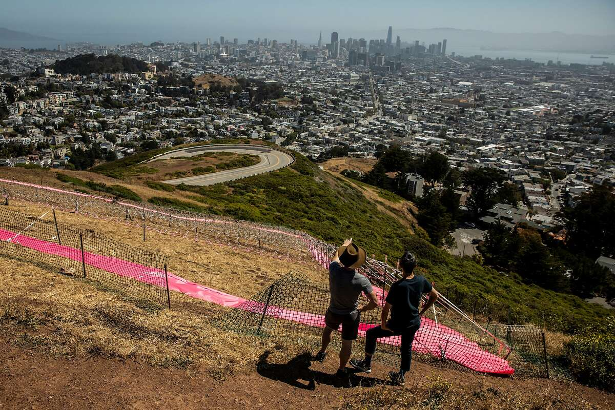 Mark Alexander (left) and Martin Hsu pause in front of the Pink Triangle Memorial on the slope of Twin Peaks on Sunday, their 14th anniversary.