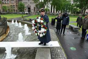 Chaplain of New Haven American Legion Post 210 Britt Conroy carries a wreath across the fountain at the World War I Memorial during a Memorial Day ceremony on the New Haven Green on May 30, 2021.