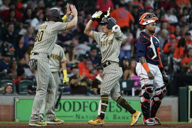 San Diego Padres third baseman Ha-Seong Kim high fives first baseman Eric Hosmer (30) as he scores past Houston Astros catcher Martin Maldonado (15) after hitting a home run during the ninth inning of a major league baseball game Sunday, May 30, 2021, at Minute Maid Park in Houston. Photo: Brett Coomer, Staff Photographer / © 2021 Houston Chronicle