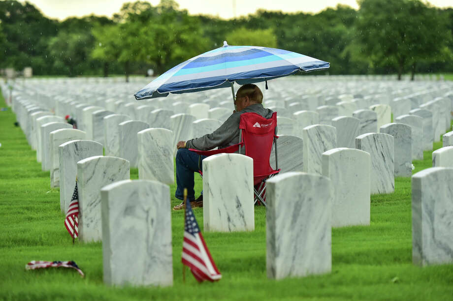 Larry Haven sits under an umbrella next to the head- stone of his wife, Margaret, early Saturday at Fort Houston National Cemetery. A retired Army staff ser- geant, he has visited the site every day since her death four years and five months ago. Because of COVID-19, Veterans Affairs is keeping the public away from a brief Memorial Day wreath-laying ceremony. Photo: Robin Jerstad / Robert Jerstad