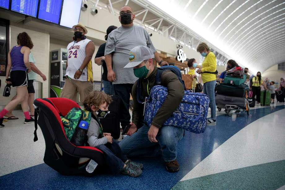 Dimas Espinola holds his cellphone so his son can watch a movie while they wait to check in for their flight at San Antonio International Airport. The long holiday weekend marks a sharp contrast from a year ago when trips were canceled. Photo: Jessica Phelps, San Antonio Express-News / **MANDATORY CREDIT FOR PHOTOG AND SAN ANTONIO EXPRESS-NEWS/NO SALES/MAGS OUT/TV  © 2021 San Antonio Express-News