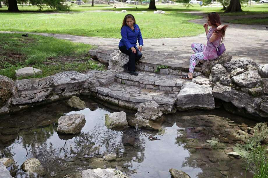 Diana Amador Luna, 56, left, talks with her daughter, Rochelle Llamas, 36, by a spring at San Pedro Springs Park. Water flows through the springs when the J-17 well hits the 655-foot mark. The well is the region's marker for the Edwards Aquifer level. Photo: Jerry Lara, San Antonio Express-News / **MANDATORY CREDIT FOR PHOTOG AND SAN ANTONIO EXPRESS-NEWS/NO SALES/MAGS OUT/TV   © 2019 San Antonio Express-News