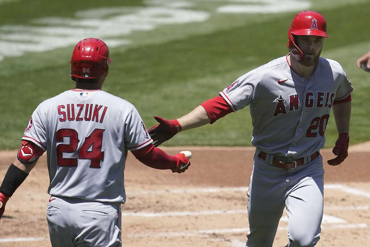 Los Angeles Angels' Jared Walsh, right, is congratulated by Kurt Suzuki after hitting a solo home run during the second inning of a baseball game against the Oakland Athletics in Oakland, Calif., Sunday, May 30, 2021. (AP Photo/Jeff Chiu)