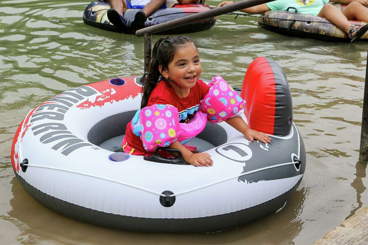 Nadali Hernandez, 4, tries to coax her parents into joining her in the water at Prince Solms Park in New Braunfels during the official start of tubing season on the Comal and Guadalupe rivers on Sunday, May 30, 2021.