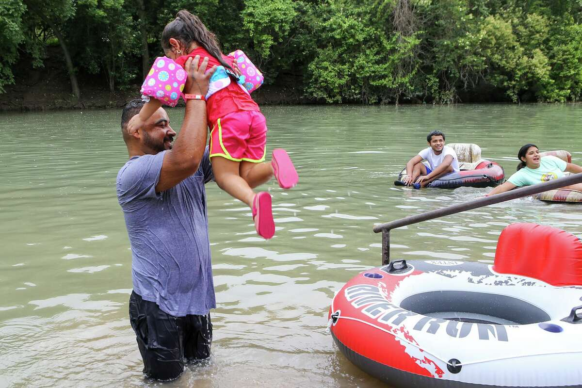 Ruben Hernandez hoists his daughter, Nadali Hernandez, 4, into the air as they begin a family trip down the Comal River at Prince Solms Park in New Braunfels during the official start of tubing season on the Comal and Guadalupe rivers on Sunday, May 30, 2021.