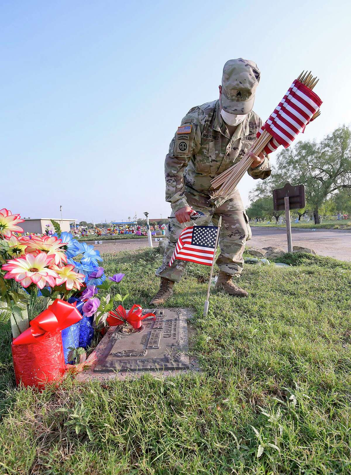 National Guardsman, Sgt. Raymond Martinez, replaces American Flags on the graves of fallen veterans at the Calvary Catholic Cemetery in 2020 before Memorial Day.