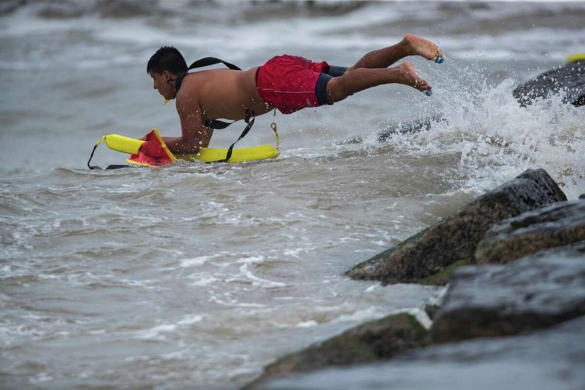 A Galveston Island Beach Patrol trainee into the Gulf of Mexico at the Galveston Seawall as part of his training during an afternoon of rough weather, Wednesday, May 19, 2021. It was the first time the trainees did the jump as part of their training.