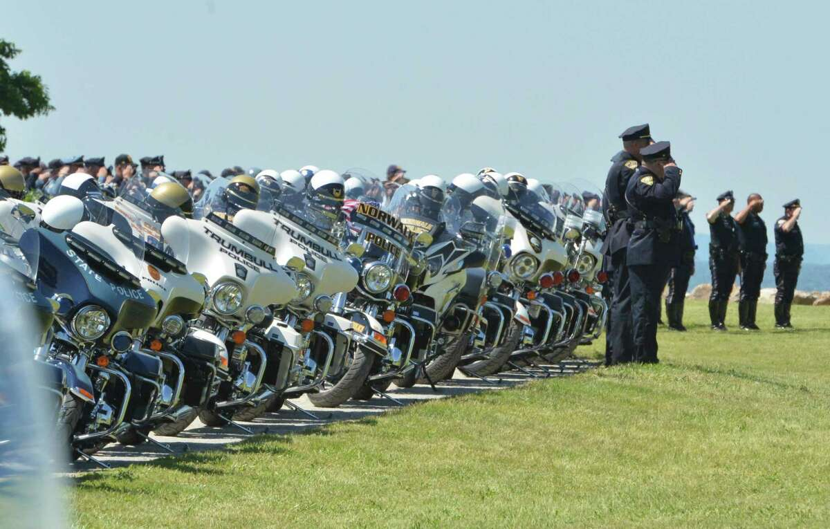 Police officers salute near the long line of parked motorcycles during the funeral service for Connecticut State Trooper First Class Walter Greene Jr. at Sherwood Island State Park on Tuesday June 12, 2018, in Westport, Conn.