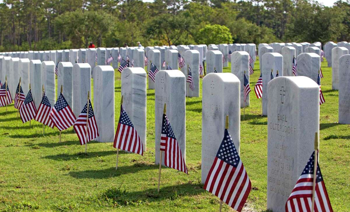 Volunteers walk as flags stand alongside headstones of members of the military at the South Florida National Cemetery Sunday, May 30, 2021 in Lake Worth, Fla.