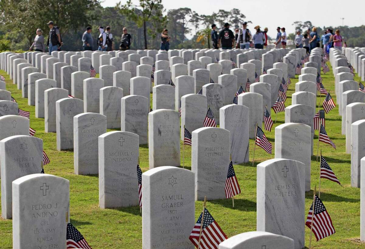 A group of volunteers walk as American flags stand alongside headstones of members of the military at the South Florida National Cemetery Sunday, May 30, 2021 in Lake Worth, Florida, Volunteers at the cemetery placed U.S. flags on some 25,000 graves, where members of the military are buried, in preparation for a Memorial Day ceremony on Monday. (David Santiago/Miami Herald/TNS)