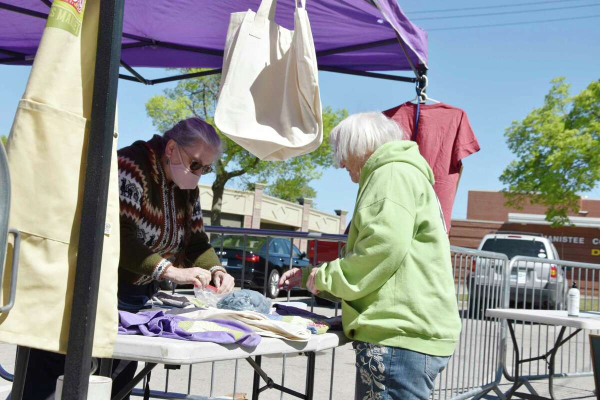 (From left) Market Manager Ramona DeGeorgio-Venegas helps a patron with a purchase of market merchandise for sale at the entrance area on Saturday. (Arielle Breen/News Advocate)