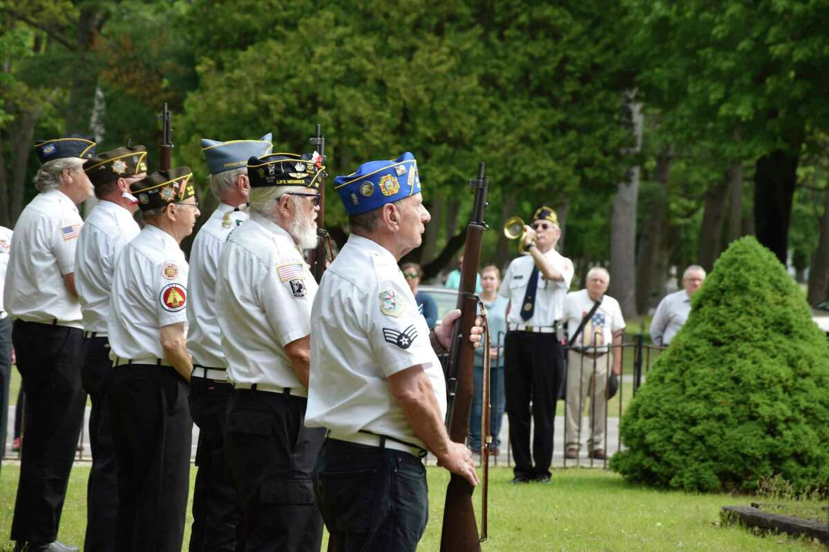 Mick Szymanski (right center) played taps during a Memorial Day ceremony on Monday at Trinity Cemetery.(Arielle Breen/News Advocate)