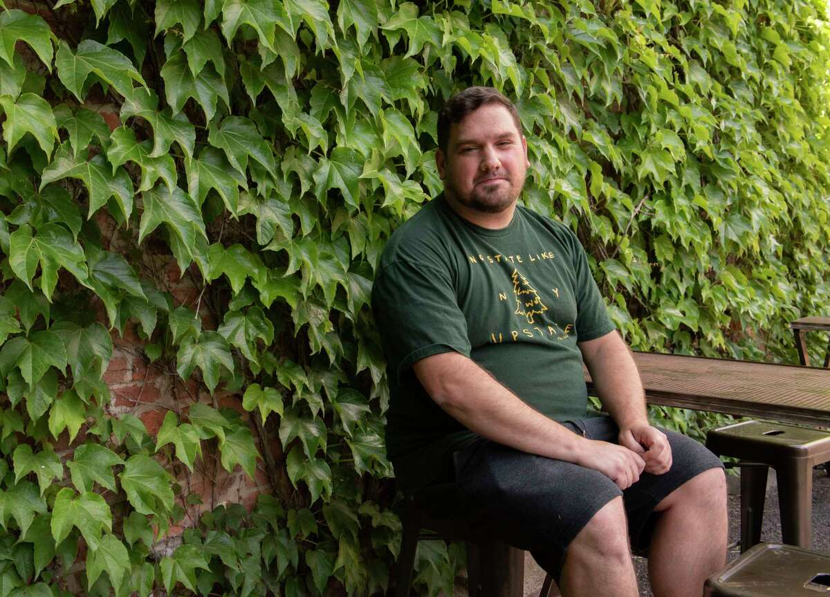 Sales director Greg Back sits in the back outdoor seating area at Rare Form Brewing in Troy.