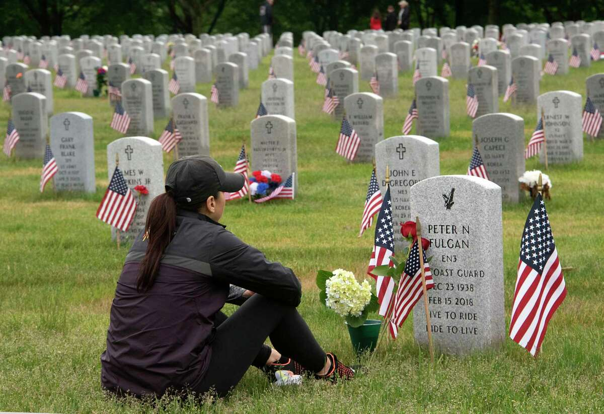 Toni Howard of Clifton Park sits by the grave of her father Peter Fulgan Jr. who served in the Coast Guard on Memorial Day at Saratoga National Cemetery Monday, May 31, 2021 in Schuylerville, N.Y. (Lori Van Buren/Times Union)