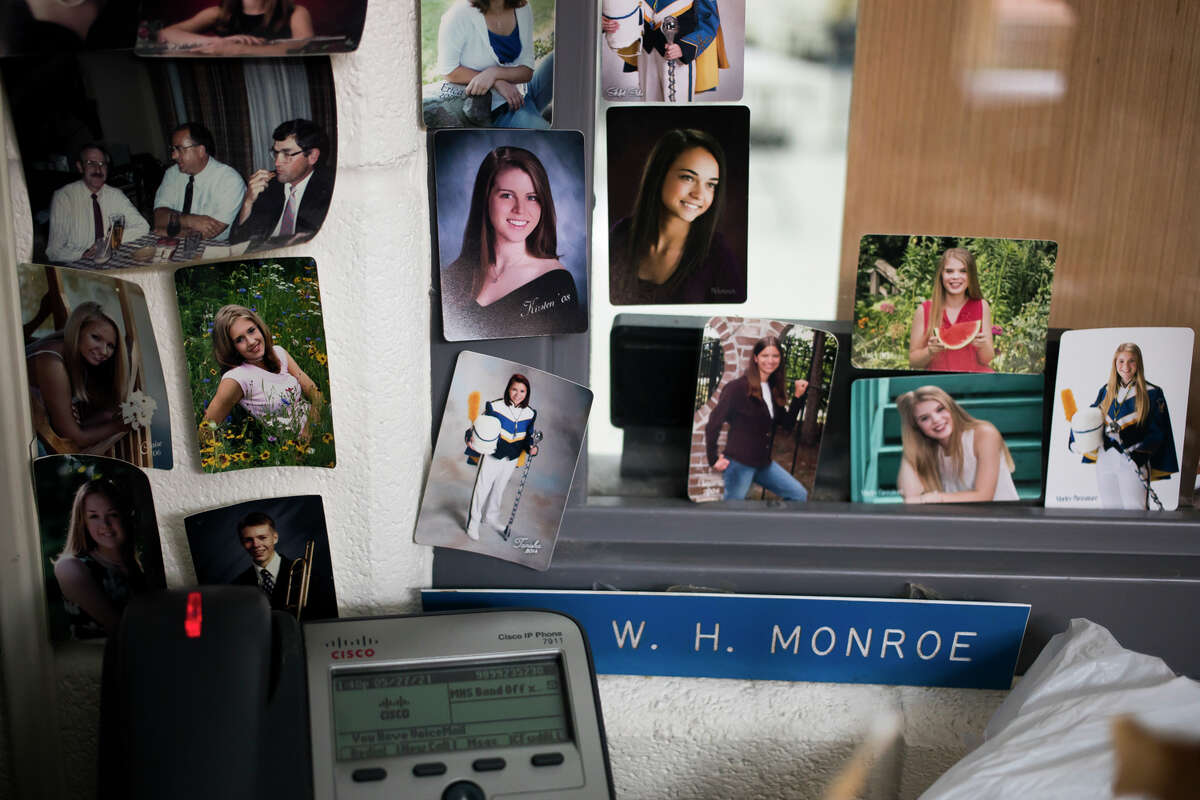 Photos of former students hang from the wall in the office of Midland High School band director William