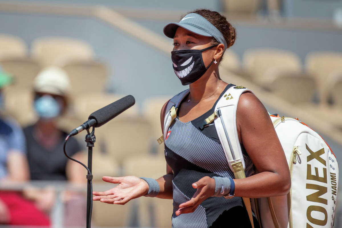 Naomi Osaka conducts an on court interview wearing a mask after her victory against Patricia Maria Tig of Romania in the first round of the Women's Singles competition at the 2021 French Open.