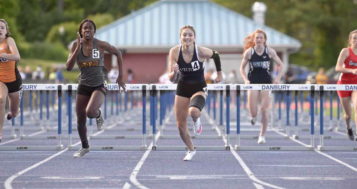 Wilton's Shelby Dejana (lane 4) and St. Joseph's Nia Christie (lane 5) finished first and second in the 100-meter hurdles final at the FCIAC championships May 24.