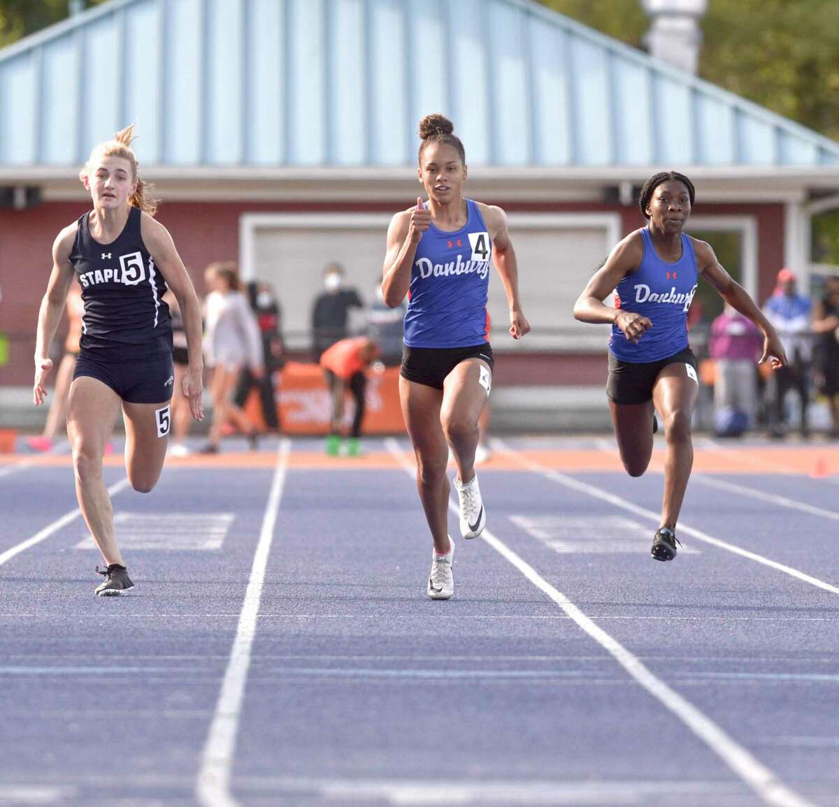 Danbury's Alanna Smith, center, finished first in the 100 meter dash at the FCIAC championships May 24.