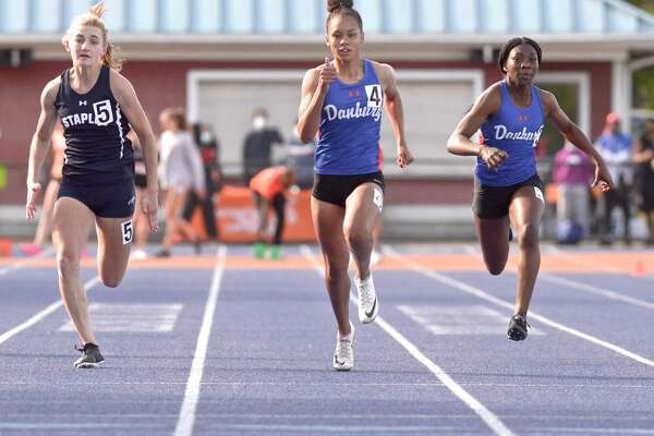 Danbury's Alanna Smith, center, finished first in the 100 meter dash at the FCIAC championship pn May 24. Staples' Francine Stevens, left, and Danbury's Florence Dickson, right, follow.