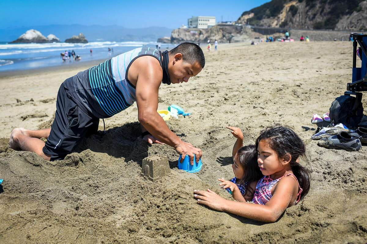 Tyrone Keller of Sacramento and his daughters, Nayeli Keller (right), age 9, and Mia Keller (second from right), age 4, play in the sand at Ocean Beach in San Francisco, Calif. on Monday, May 31, 2021. Tyrone said he was looking to escape the heat in Sacramento for the day.