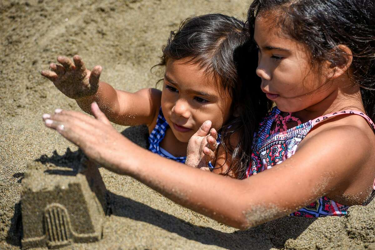 Sisters Nayeli Keller (right) age 9, and Mia Keller (center), age 4, play in the sand at Ocean Beach in San Francisco, Calif. on Monday, May 31, 2021. Tyrone Keller, their father, said he was looking to escape the heat in Sacramento for the day.