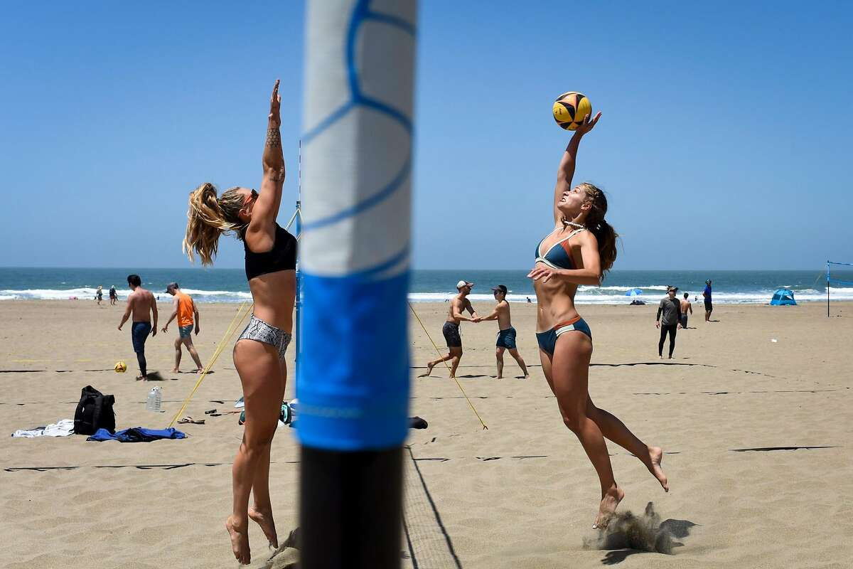 Alicia Ponzani of San Francisco jumps to hit the ball while Say Arena, also of San Francisco, prepares to block while playing in a San Francisco Beach Volleyball pickup league match at Ocean Beach in San Francisco, Calif. on Monday, May 31, 2021. The pickup league hosts beach matches, clinics, and tournaments.