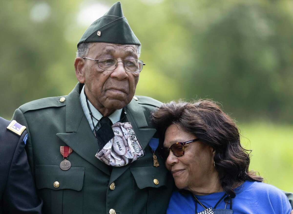 Eva Hollins rests her head on her husbands chest, Pfc. Romie Hollins during the 4th Annual Memorial Day Celebration at the Sweet Rest Cemetery, Monday, May 31, 2021, in Tamina. The cemetery was officially designated as a historical area after a nine-month long process led by the The Tamina Cemetery and Community Project CDC.