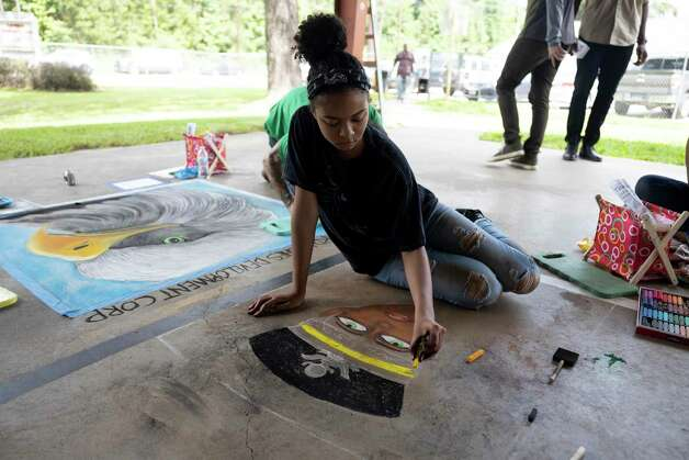 Rylan Thomas, 13, draws with chalk during the 4th Annual Memorial Day Celebration at Tamina Park Community Building, Monday, May 31, 2021, in Tamina. The cemetery was officially designated as a historical area after a nine-month long process led by the The Tamina Cemetery and Community Project CDC. Photo: Gustavo Huerta, Houston Chronicle / Staff Photographer / Houston Chronicle © 2021