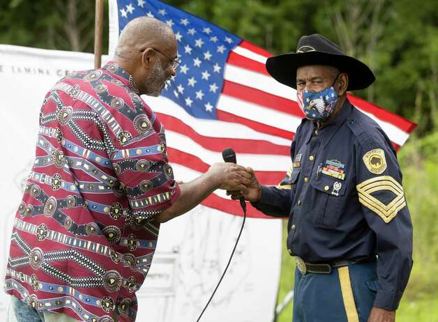 Sgt. Major James Williams, with the Buffalo Soldiers Museum, right, is handed the microphone by Elijah Easley during the 4th Annual Memorial Day Celebration at the Sweet Rest Cemetery, Monday, May 31, 2021, in Tamina. The cemetery was officially designated as a historical area after a nine-month long process led by the The Tamina Cemetery and Community Project CDC. Photo: Gustavo Huerta, Houston Chronicle / Staff Photographer / Houston Chronicle © 2021