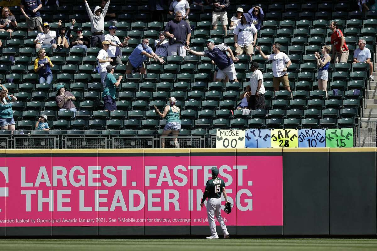 Oakland Athletics right fielder Seth Brown watches a home run by Seattle Mariners' Donovan Walton drop into the stands among fans during the fourth inning of Monday's game.