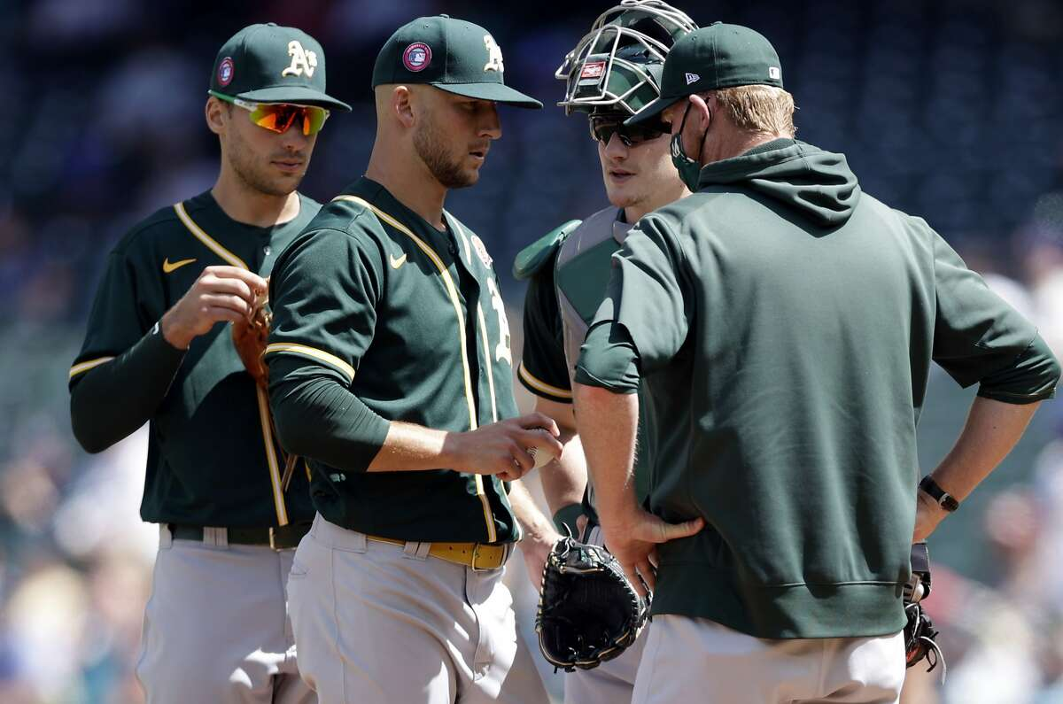 Oakland Athletics starting pitcher James Kaprielian, second from left, talks on the mound with pitching coach Scott Emerson, right, during the fourth inning of a baseball game against the Seattle Mariners, Monday, May 31, 2021, in Seattle. (AP Photo/John Froschauer)