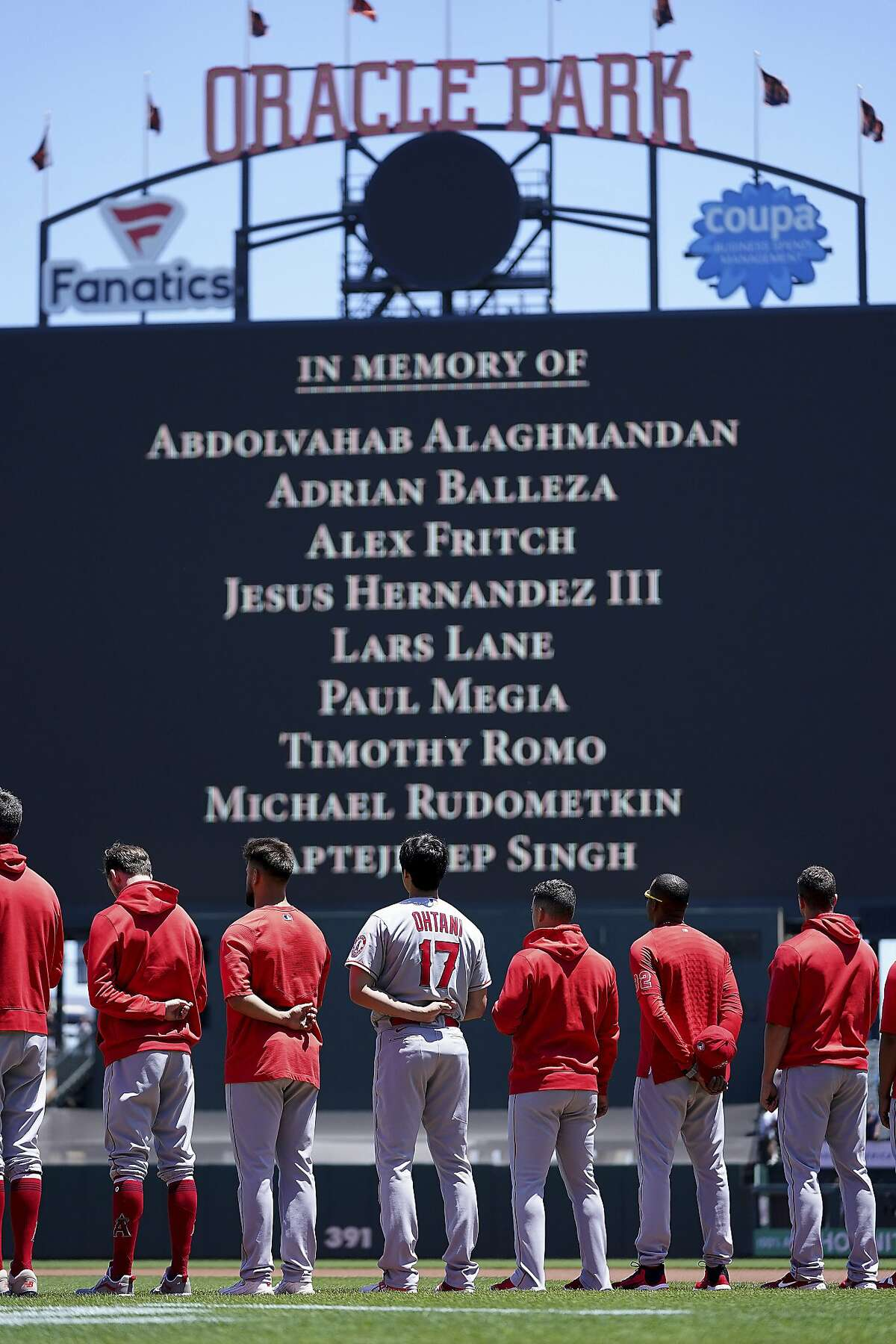 Players observe a moment of silence to honor the shooting victims from San Jose, Calif., before a baseball game between the San Francisco Giants and the Los Angeles Angels, Monday, May 31, 2021, in San Francisco. (AP Photo/Tony Avelar)
