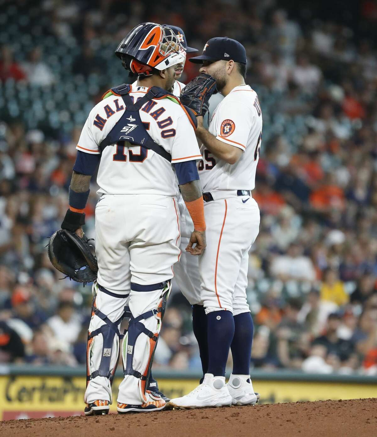 Houston Astros starting pitcher Jose Urquidy (65) chats with catcher Martin Maldonado (15) and Carlos Correa during the sixth inning of an MLB baseball game at Minute Maid Park, Monday, May 31, 2021, in Houston.