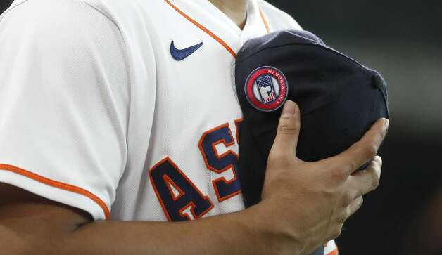 Houston Astros second baseman Robel Garcia holds his cap with a special Memorial Day patch during the national anthem before a baseball game against the Boston Red Sox, Monday, May 31, 2021, in Houston. (Karen Warreen/Houston Chronicle via AP) Photo: Karen Warren/Associated Press / @2021 Houston Chronicle