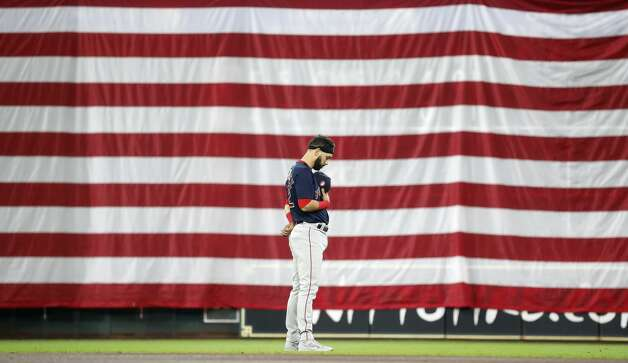Boston Red Sox Marwin Gonzalez during a moment of silence in front of the giant American flag over the scoreboard under the Crawford Boxes during the National Anthem before the start of an MLB baseball game at Minute Maid Park, Monday, May 31, 2021, in Houston. Photo: Karen Warren/Staff Photographer / @2021 Houston Chronicle