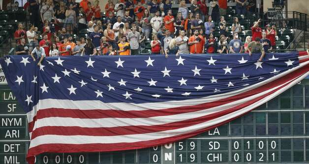 Houston Astros employees lower the giant American flag over the scoreboard under the Crawford Boxes during the National Anthem before the start of an MLB baseball game at Minute Maid Park, Monday, May 31, 2021, in Houston. Photo: Karen Warren/Staff Photographer / @2021 Houston Chronicle