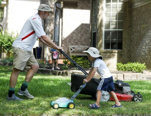 """Grayson Moore, 5, helps his dad, Seth, mow their front yard with his toy lawnmower on Memorial Day, Monday, May 31, 2021, in Kingwood. Grayson can be seen wearing a floppy hat, protective goggles and following behind his father with his green and yellow plastic mower every weekend. """"He started back when he was three and just really enjoys helping me around the yard whether it's trimming the trees, weeding, or mowing the yard,"""" Seth Moore said. Photo: Jason Fochtman/Staff Photographer / 2021 ? Houston Chronicle"""