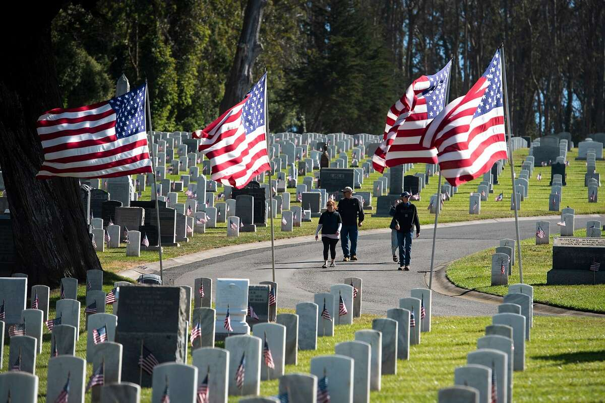 People walk through San Francisco National Cemetery in San Francisco, Calif. on Memorial Day, Monday, May 31, 2021.