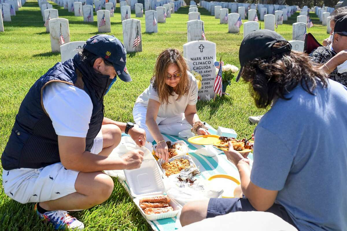 """Bing Chacker, left, Maria Lourdes Millare, her husband, Gilbert Millare, and Maria's parents, Arthur Climaco and Teresita Climaco, set up a picnic next to the grave of Mark Ryan Climaco Caguioa, the son of Maria and Gilbert, at San Francisco National Cemetery in San Francisco, Calif. on Memorial Day, Monday, May 31, 2021. Mark died on May 24, 2007 from injuries while serving in Bhagdad, Iraq, at the age of 21. Maria said the family came to honor not only her son, """"but also the other service men and women."""""""