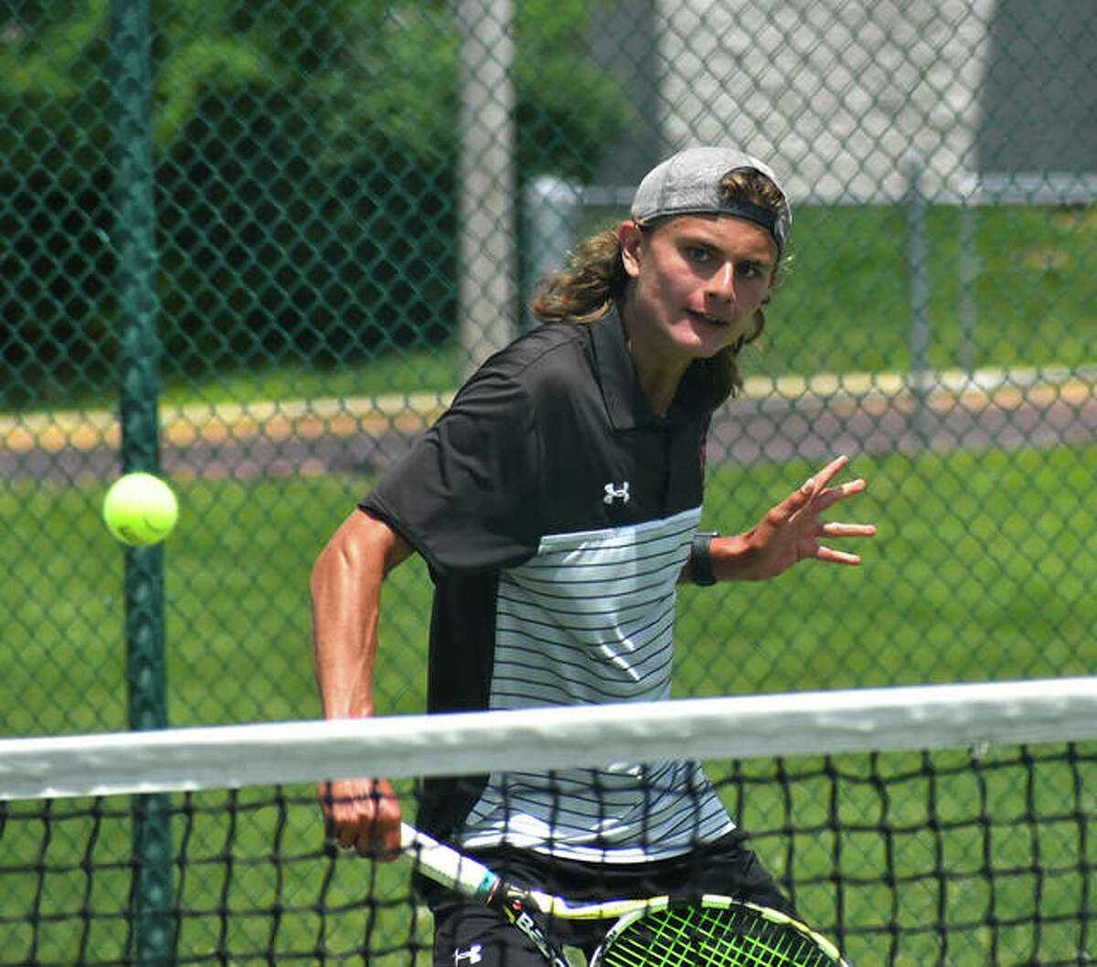 Edwardsville's Jace Ackerman takes a little off his backhand shot in his No. 4 singles championship match at the Southwestern Conference Tournament on Monday in O'Fallon.