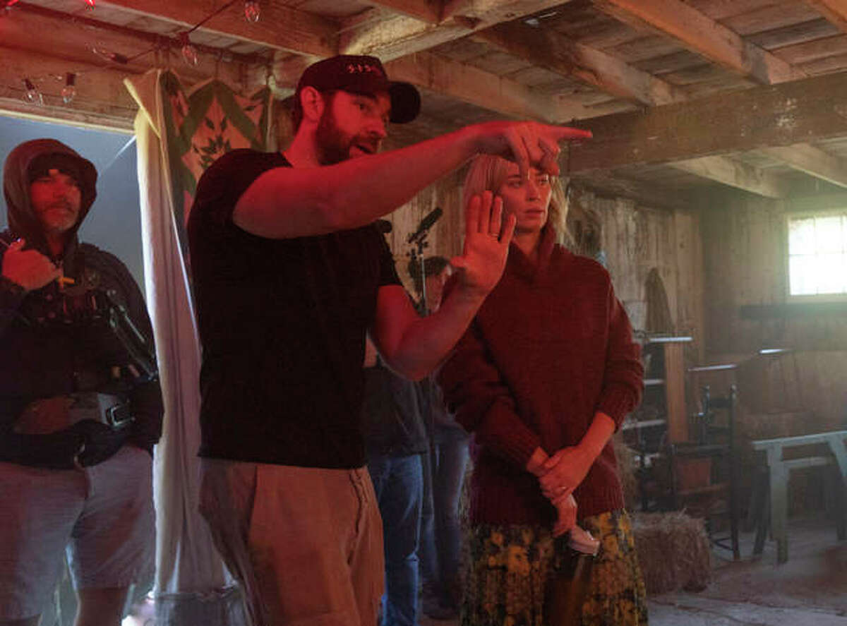 This image released by Paramount Pictures shows director John Krasinski, left, and Emily Blunt on the set of