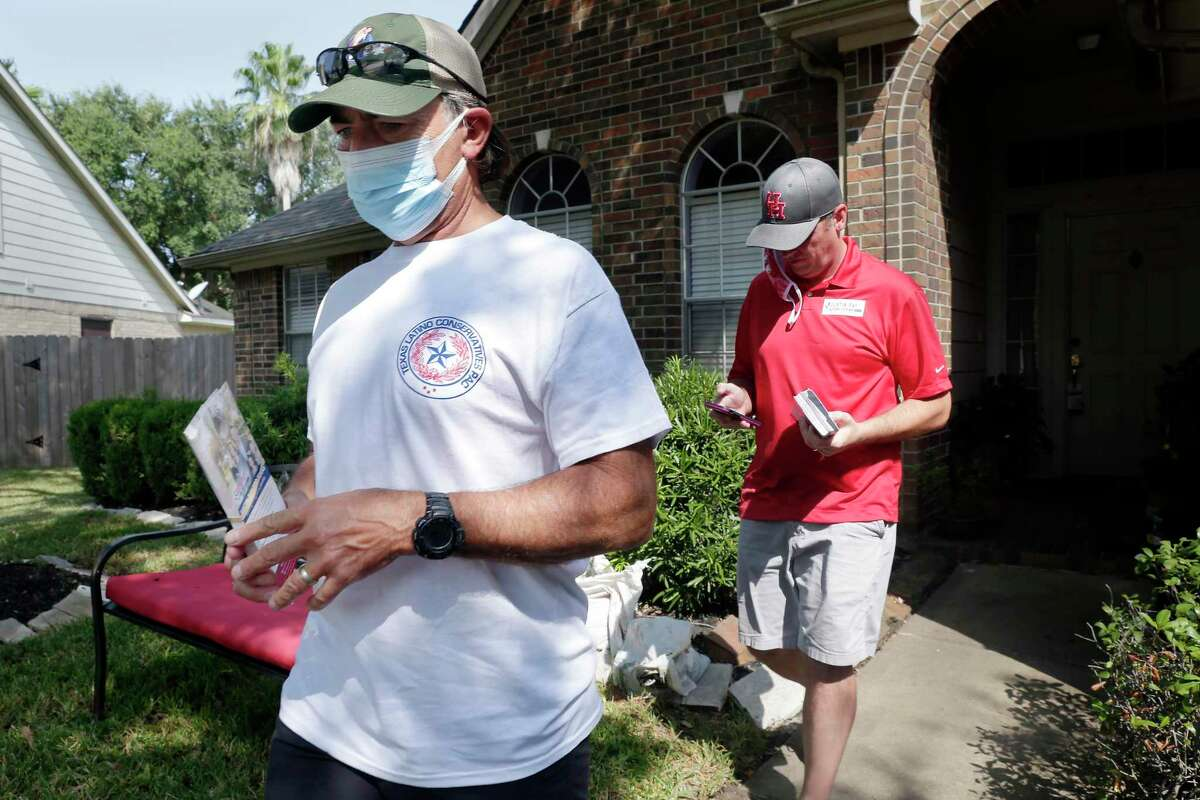 Texas Latino Conservatives founder Orlando Sanchez, left, and candidate Justin Ray, right, move to the next front door as they block walk house to house campaigning for Ray in a residential subdivision Saturday, Sep. 19, 2020 in Cypress, TX.
