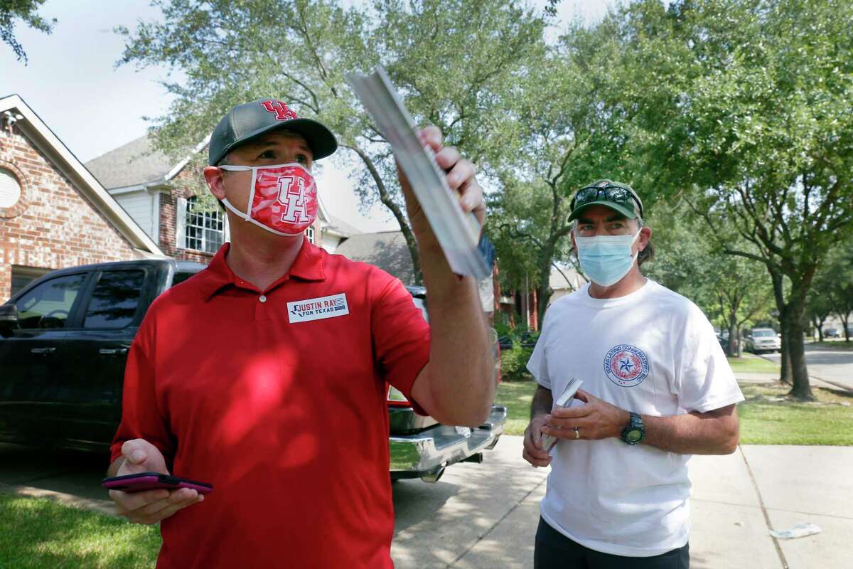 Candidate Justin Ray, left, and Texas Latino Conservatives founder Orlando Sanchez, right, get their bearing as they block walk house to house campaigning for Ray in a residential subdivision Saturday, Sep. 19, 2020 in Cypress, TX.