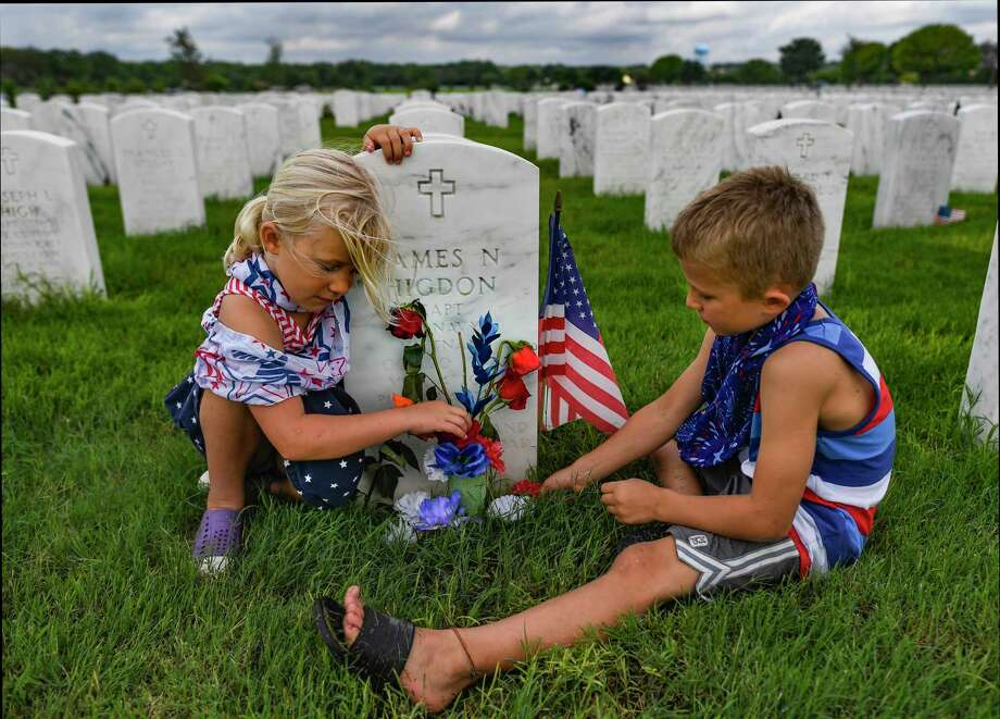Myra Baer, 5, left, and her brother, Ellison, 7, visit the gravesite of Navy pilot Capt. James Higdon, a member of their church. Photo: Billy Calzada / Staff Photographer / `