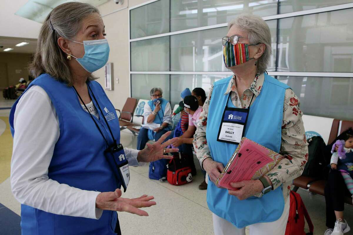 Barbara Edens, left, talks with fellow Interfaith Welcome Coalition volunteer, Sally Andrade, while helping migrants at the San Antonio International Airport on Wednesday. The volunteers help the migrants make their connections to final destinations and offer aid, toiletries and temporary housing when needed.