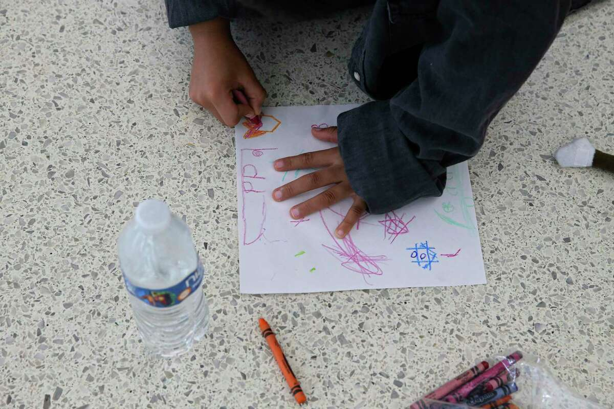 A child migrants colors while waiting for a flight at the San Antonio International Airport with his father Wednesday. Volunteers with the Interfaith Welcome Coalition help the migrants make their connections to final destinations and offer aid, toiletries and temporary housing when needed.