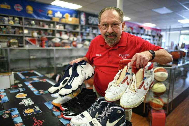 Charlie DiPietro opened Sports Cards Plus in 1992. His shop features countless items of memorabilia, including cards, helmets, autographed sneakers, signed baseballs and more. Here, he holds shoes worn by Hall of Famers David Robinson, right, and Tim Duncan at left.