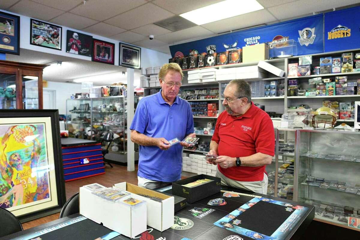 Charlie DiPietro, right, owner of Sports Cards Plus, discusses baseball and football cards with Don Booker. The cards date from Booker's childhood in the 1950s and 1960s.